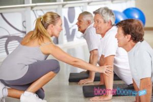46042969 - fitness instructor helping senior people in gym during back training class